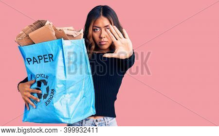 Young beautiful mixed race woman holding recycling wastebasket with paper and cardboard with open hand doing stop sign with serious and confident expression, defense gesture