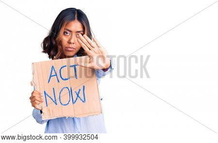 Young beautiful mixed race woman holding act now banner with open hand doing stop sign with serious and confident expression, defense gesture