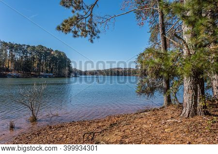 A Man Standing In A Boat Fishing On Lake Lanier In Georgia In The Distance From The Shoreline On A B