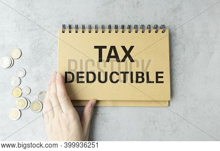 Closeup On Businessman Holding A Card With Text Tax Deductible, Business Concept Image With Soft Foc