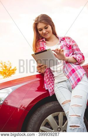 Girl With A Tablet In Hands Standing Next To The Car
