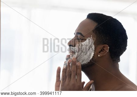 Happy Young Mixed Race Man Cleansing Face With Foamy Scrub.