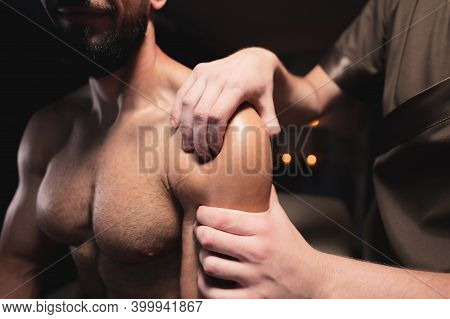 Close-up Male Shoulder And Deltoid Muscle Massage To Athlete Muscular Man In Dark Room Of Spa Salon