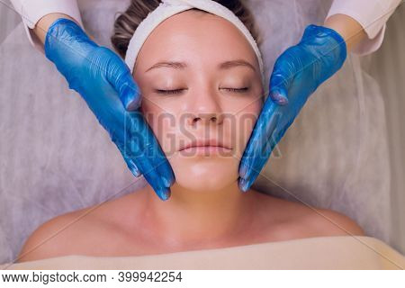 Top View Of Beautiful Young Woman Getting Face Skin Treatment. Cosmetician Is Undertaking The Proced
