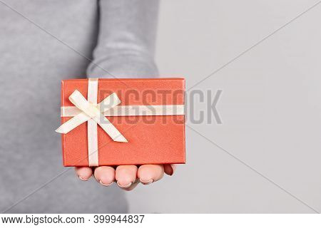 Hand With Red Giftbox On Grey Background.