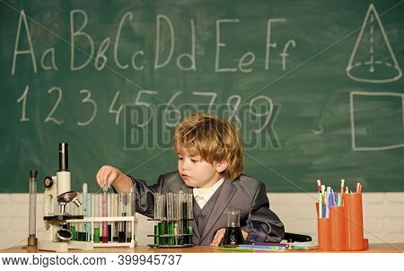Knowledge Concept. Boy Near Microscope And Test Tubes In School Classroom. Kid Study Biology Chemist
