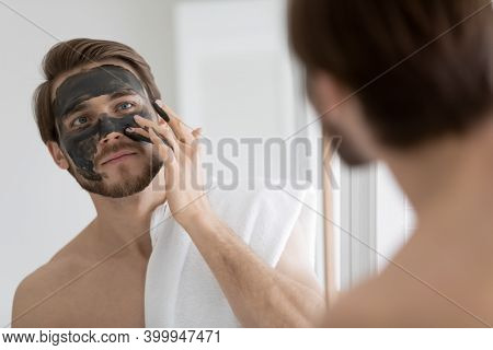 Peaceful Young Man Applying Black Charcoal Clay Mask On Face.