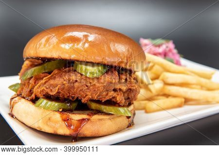 Large Pieces Of Breaded Chicken In Middle Of Stacked Sandwich Served On Bun With French Fries.