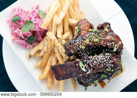 Overhead View Of Hearty Plate Stacked With Glazed Bbq Pork Ribs Served With French Fries For A Plate