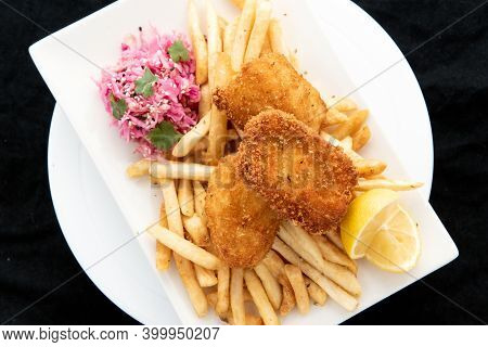 Overhead View Of Breaded Halibut Fish And Chips Served With French Fries And Lemon Garnishment For A