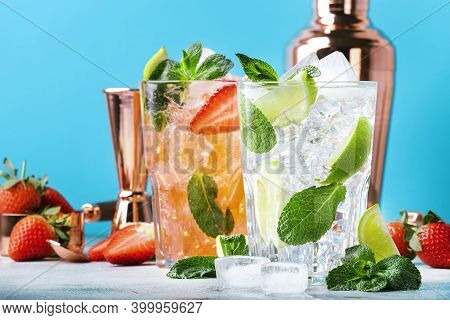 Fresh Mojito Cocktail Set With Lime, Mint, Strawberry And Ice In Glass On Blue Background. Summer Co