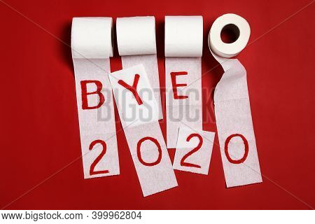 Toilet Paper With Text Bye 2020 On Red Background, Flat Lay