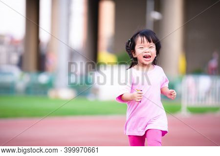 Active Child Running At The Stadium.  Happy Kid Exercise And Have Fun Laughing. Sweet Smile Cute Gir