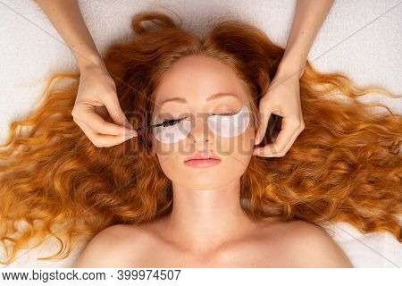 Beautiful Red-haired Girl With Curly Hair. Beautician Hands, Eyepatches With Eyelash Brush.