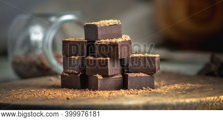 Delicious Cubes Of Bitter Dark Chocolate Strewed With Cocoa Powder On A Wooden Table