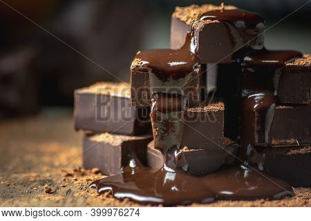 Heap Of Delicious Cubes Of Bitter Dark Chocolate Sprinkled With Cocoa Powder And Poured With Liquid