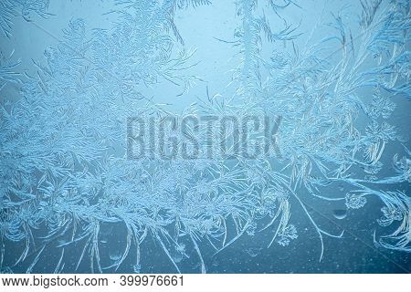 Beautiful Sparkling Natural Frost Pattern On The Blue Window Glass