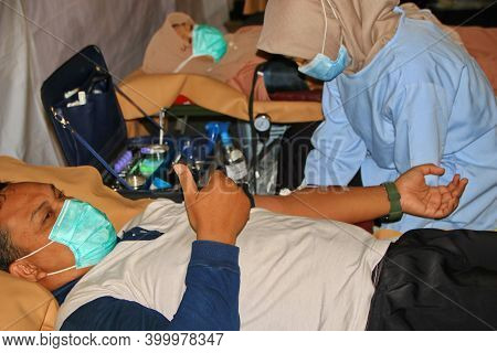 Blood Donor At Donation, Transfusion. Close Up Right Arm Of A Business Man Receiving Blood In Hospit