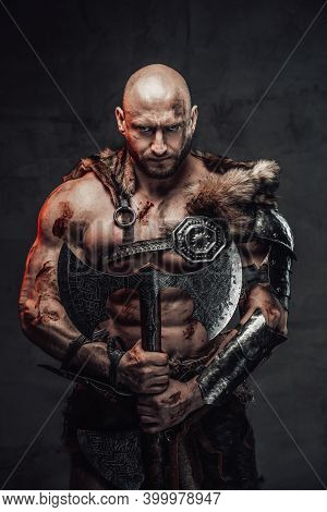 Portrait Of A Nordic Bald Warrior Armed With Two Handed Axe And In Dark Armour With Fur In Atmospher