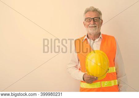Studio Shot Of Happy Senior Bearded Man Construction Worker Smiling While Holding Hard Hat And Weari