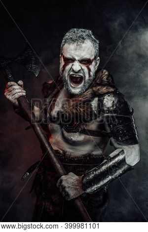Violent And Screaming Mythical Barbarian In Dark Armour With Fur Holding A Two Handed Axe In Dark Sm