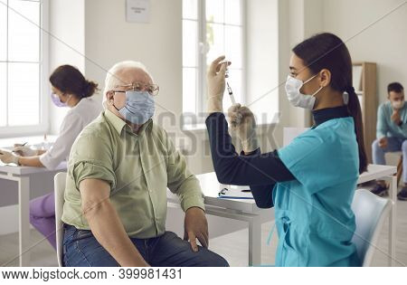 Senior Patient Waiting To Get A Shot And Looking At Young Doctor Getting The Vaccine Ready