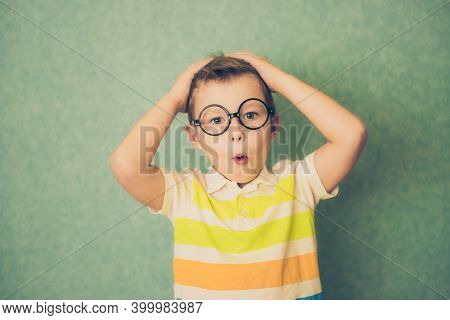 Adorable Young Boy In Shock On Blue Background. Shocked Child Looking At Camera In Disbelief. Shock,
