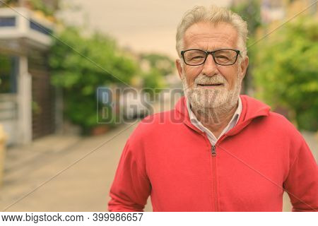 Happy Handsome Senior Bearded Man Smiling While Wearing Eyeglasses And Red Jacket Outdoors