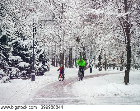 A Male Father And His Little Son Spend Their Weekend On Bicycles In Winter. Bearded Man And His Son