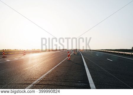 Empty Highway With Asphalt Road And Cloudy Sky