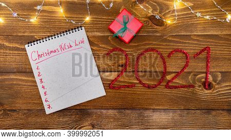 Christmas Composition Gift, Garland, Wish List And Numbers 2021. New Year On A Wooden Background. Co