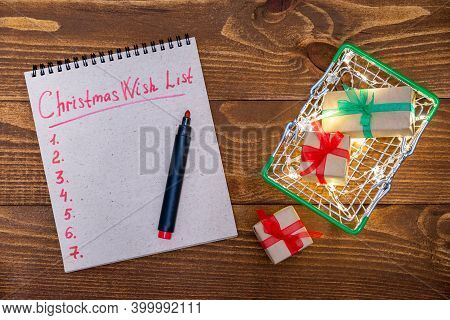Christmas Composition On A Wooden Background: Grocery Basket With Gifts, Garland, Wish List For 2021