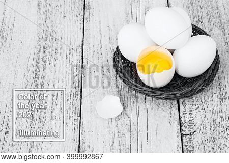 Broke One Whole Egg Amongst White Eggs In Basket On A White Background. Color Of The Year 2021
