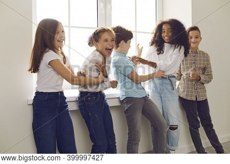 Group Of Children Playing And Laughing During Recess At School Or Fun Party At Home