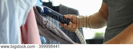 Man Is Ironing His Shirt With Steamer On Hanger. Choosing Concept Shirt Steamer