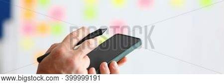 In His Hands He Holds A Smartphone And Stylus For Electronic Signature. Development Of Business Appl