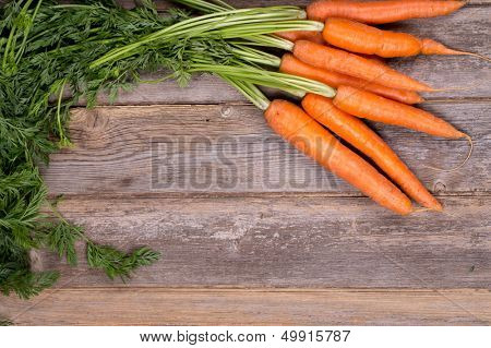 A bunch of fresh carrots on vintage style wood background