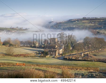 thinning mist cover revealing the church of st mary in oxenhope in the yorkshire dales