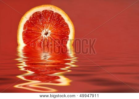 Juicy half of a blood orange in water on a red background horizontal view
