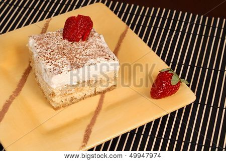 A piece of delicious tiramisu dusted with cocoa on a yellow plate with two strawberries