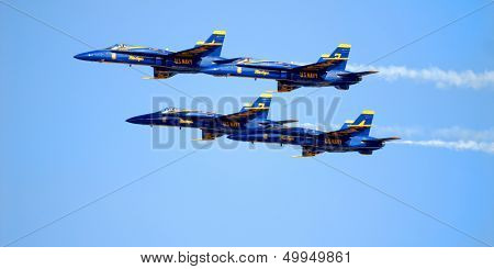 Navy FA-18 Hornets flying in a precision pattern at an air show