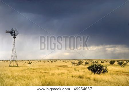 Windmill in a Texas field along Route 66 with a storm approaching