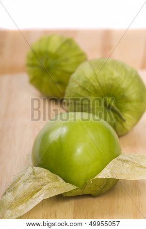 Three fresh tomatillos on a cutting board