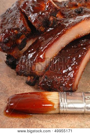 Delicious BBQ baby-back ribs with tangy sauce and a sauce brush with focus on the sauce drip