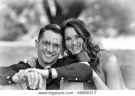 Black and White version of a happy young couple sitting on the ground in a garden setting after becoming engaged.