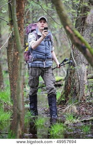 lost hiker in forest with mobile satellite navigation device - geo-caching
