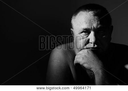 Dramatic close up portrait of depressed old man