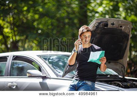 Joven guapo pidiendo ayuda con su coche por la carretera