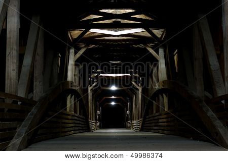 A covered bridge of Indiana reflects the light in the night.