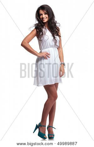full length picture of a young beautiful woman holding a hand on her hip while smiling for the camera. isolated on a white background
